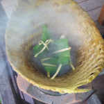Banana leaf packets of fish steaming.