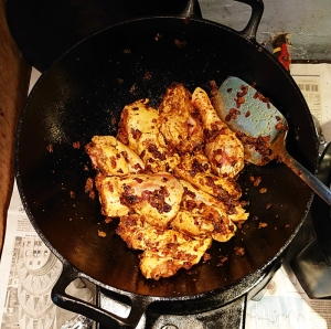 Chicken pieces in wok with masala and onions